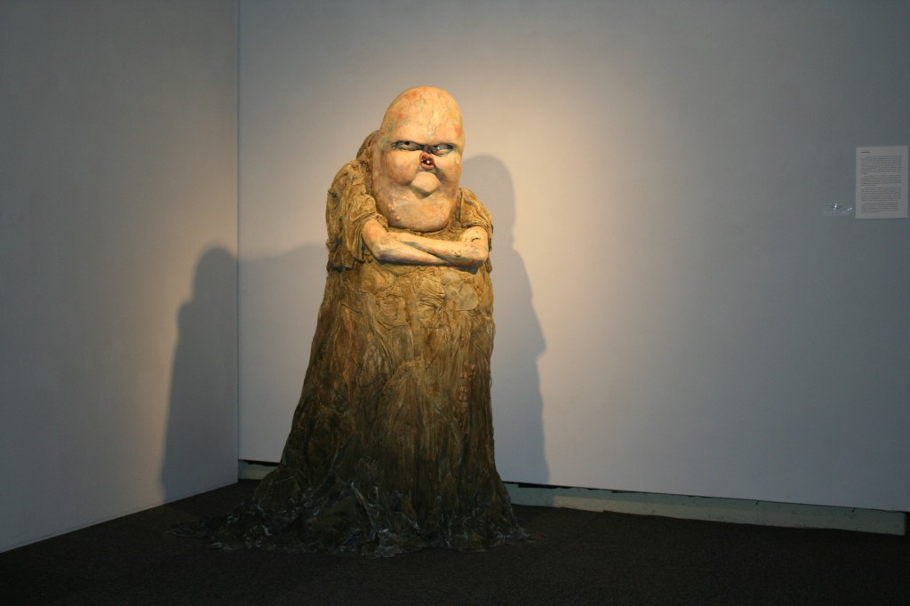 sculpture of angry creature with arms crossed