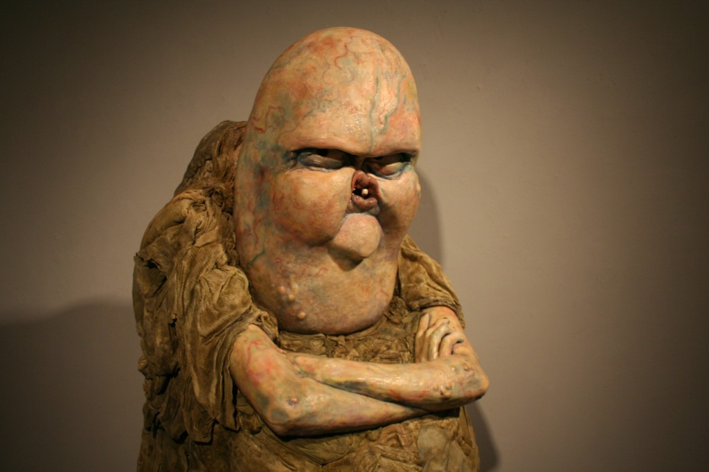 yellowish sculpture of an angry creature