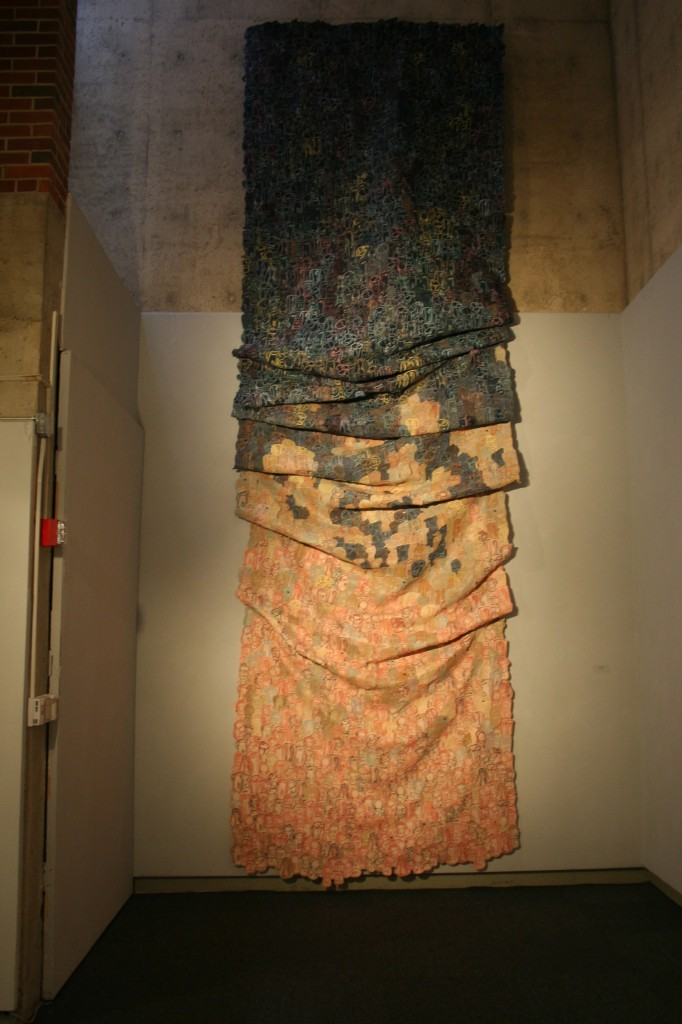 Textile work in a variety of colors up on a gallery wall