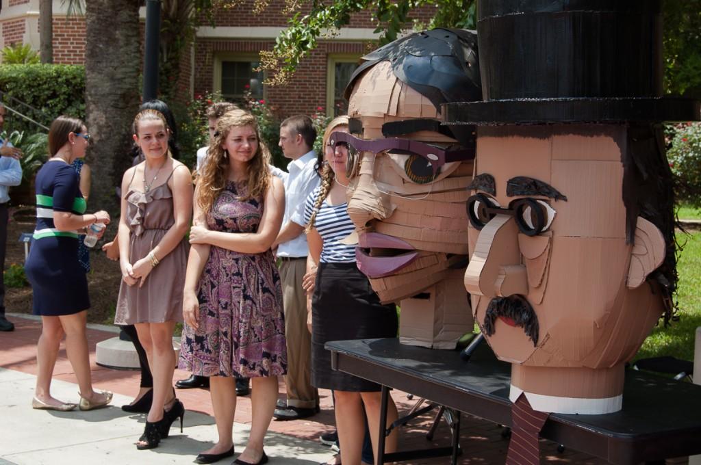 Two large cardboard heads, one female, one male
