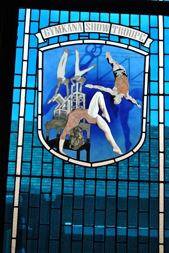 Stained glass window where gymnasts are being illustrated