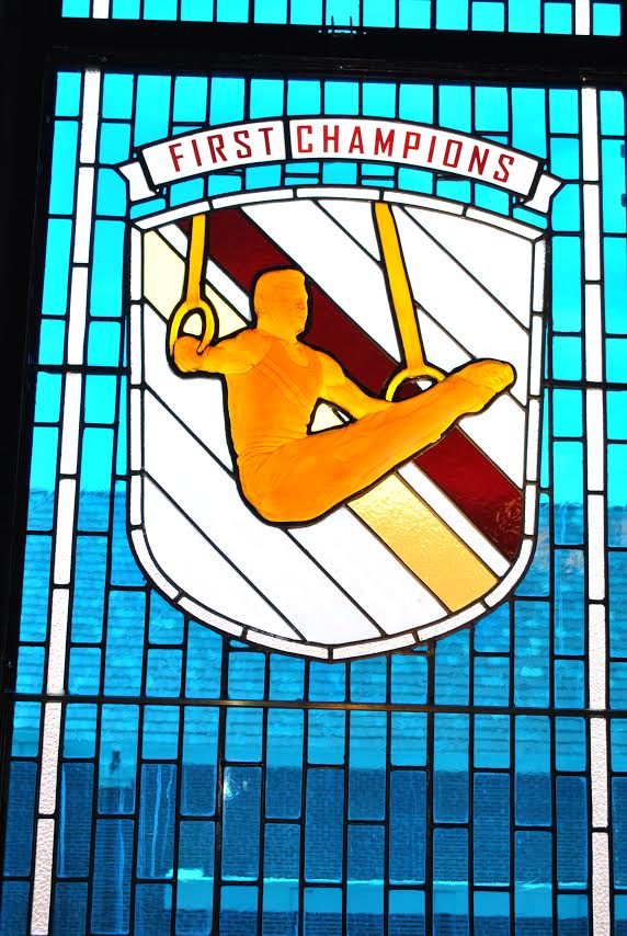 """stained glass window titled """"first champions"""" showing a gymnast"""