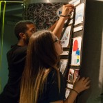 Side shot of two students hanging their project