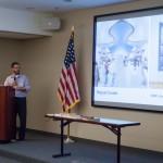 Angled shot of man giving presentation with slide