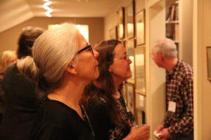 """Elece Harrison examines work on display at the January 2016 soiree """"Baade Boom Baade Bing"""""""