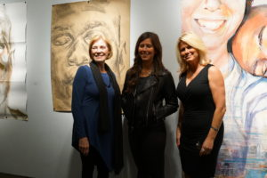 Curators Dr. Susan Baldino and Allison Leatzow with artist Mikaela Sheldt and her paintings.