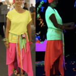 4) Joan Matey, artist and former director of the Knott House Museum, in fluorescent garb in normal light and in the blacklight installation.