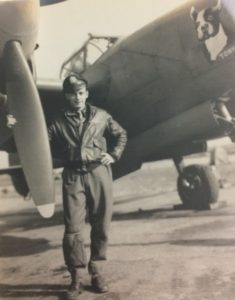 Black and white photo of man holding an airplane's propeller
