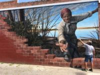 Artist MIchael Rosato, a 1983 graduate of Florida State University, applies protective coating to his mural of abolitionist Harriet Tubman in Cambridge, Maryland. (Photo: Special to the Democrat)