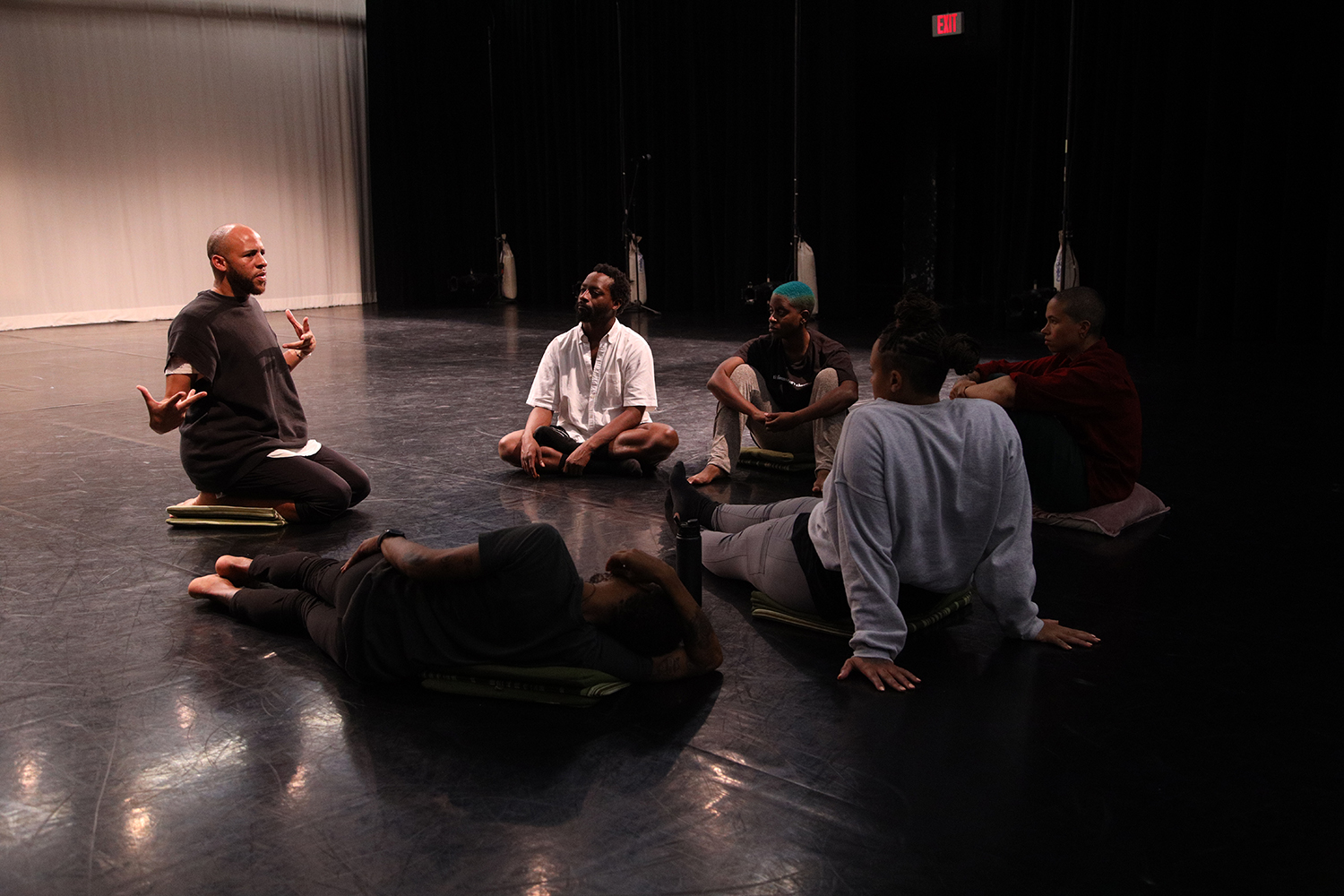 Five people sit or lay on cushions in a circle on a black floor, engaged in a rehearsal discussion, led by a person sitting upright and gesturing surrounded by black curtains and a white scrim.